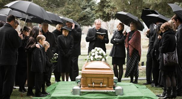 the-funeral-director-with-the-priest-at-a-graveside-service
