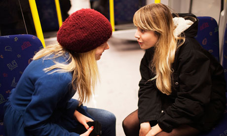 Two teenage girls talking on subway train