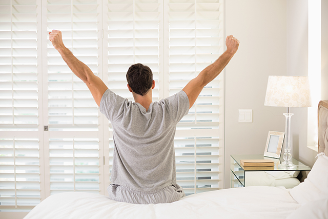 Rear view of a young man waking up in bed and stretching his arms
